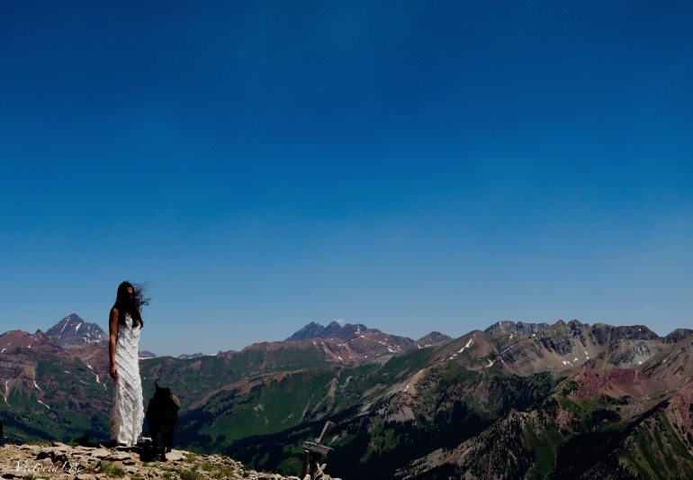 Victoria Lise stand atop Gothic mountain in MinkPink white lace dress