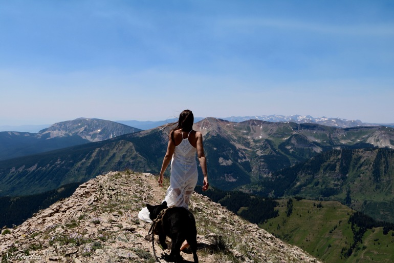Victoria Lise walks peak trail on gothic mountain in MinkPink lace dress