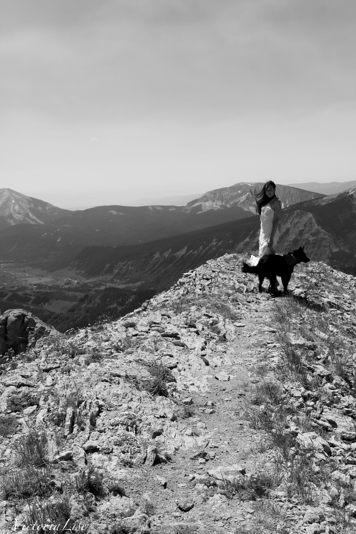 Victoria Lise on summit of gothic mountain with dog, Styx in black and white.