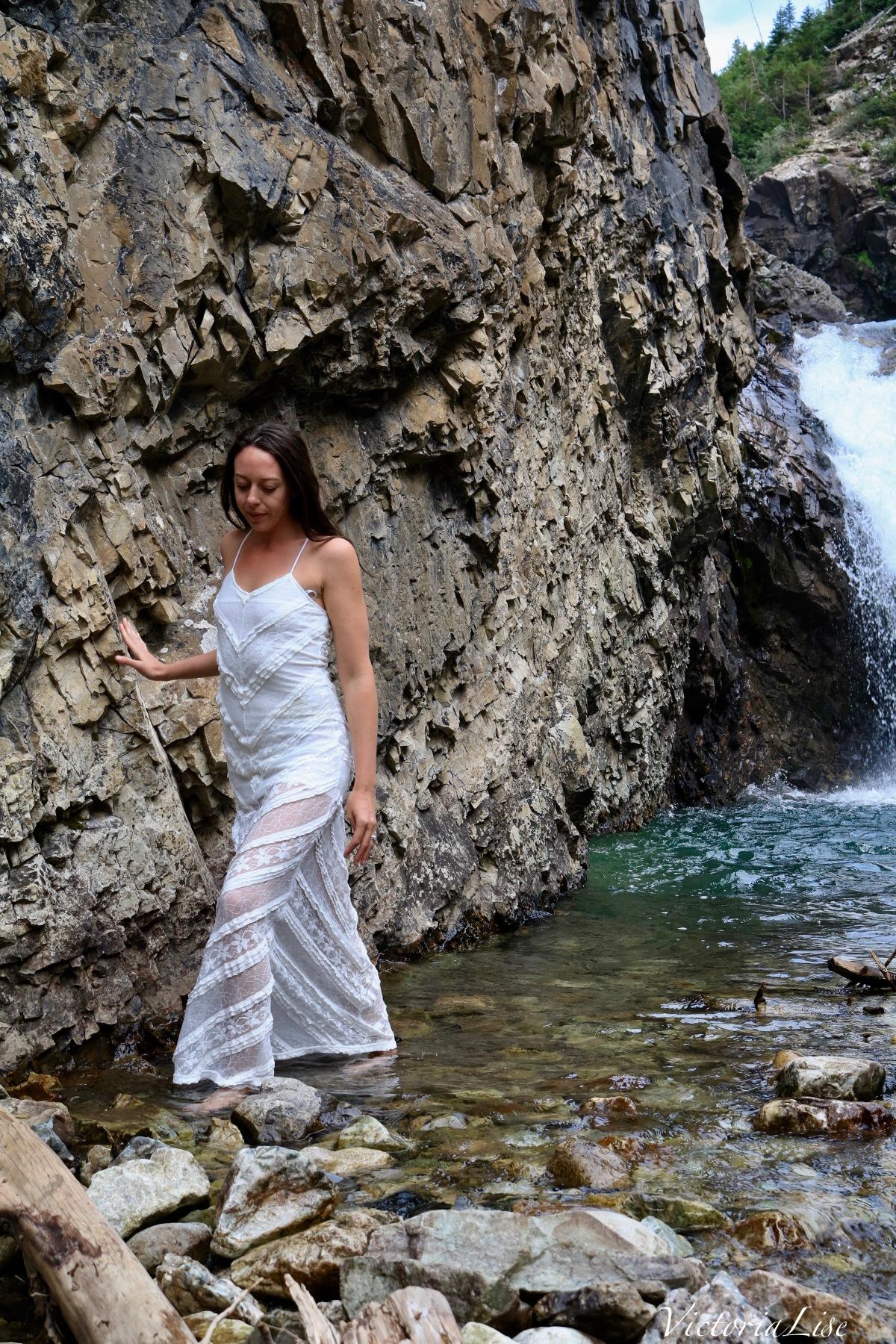 Victoria Lise walks in alpine water wearing lace dress