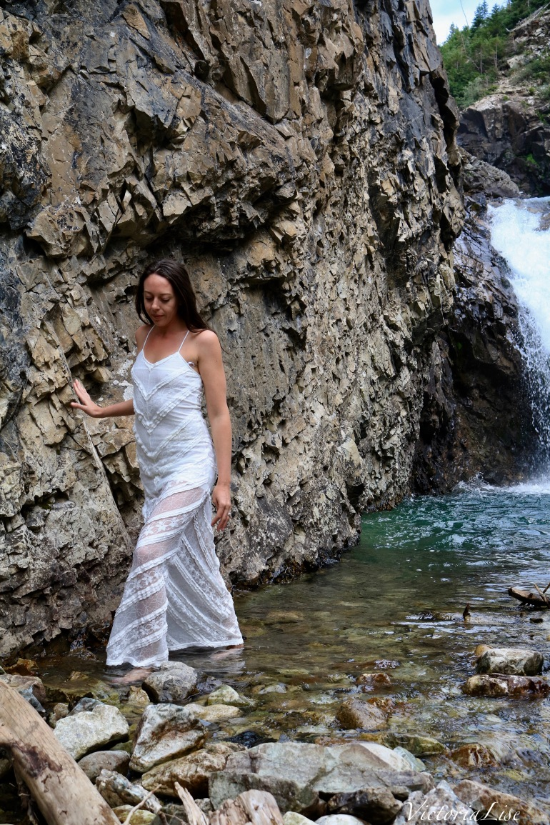 Victoria Lise walks in alpine water wearing lace dress