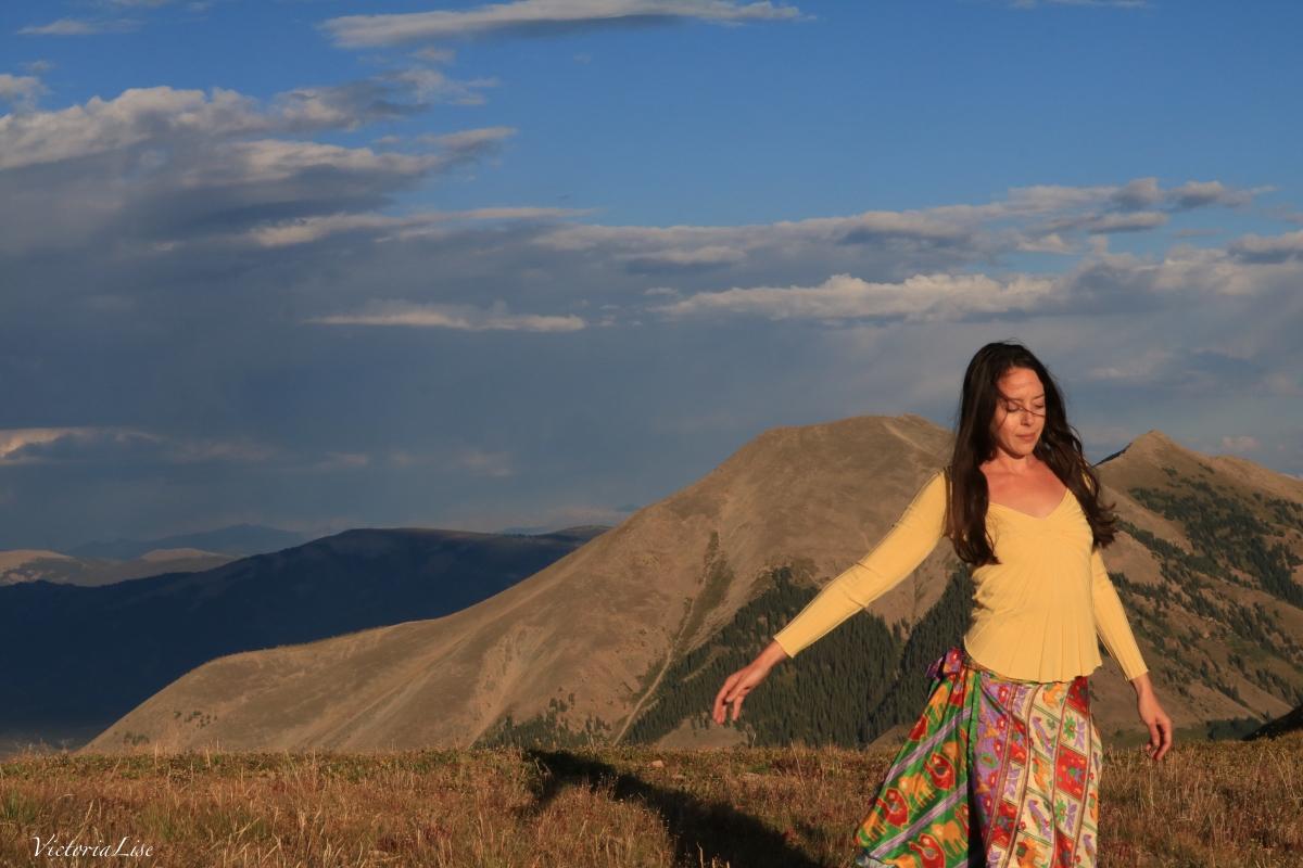 Victoria Lise atop summit at sunset