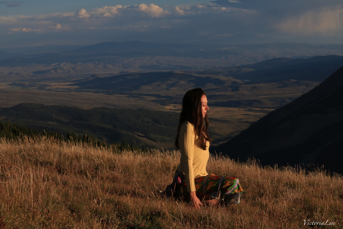 Victoria Lise mediates at sunset atop summit