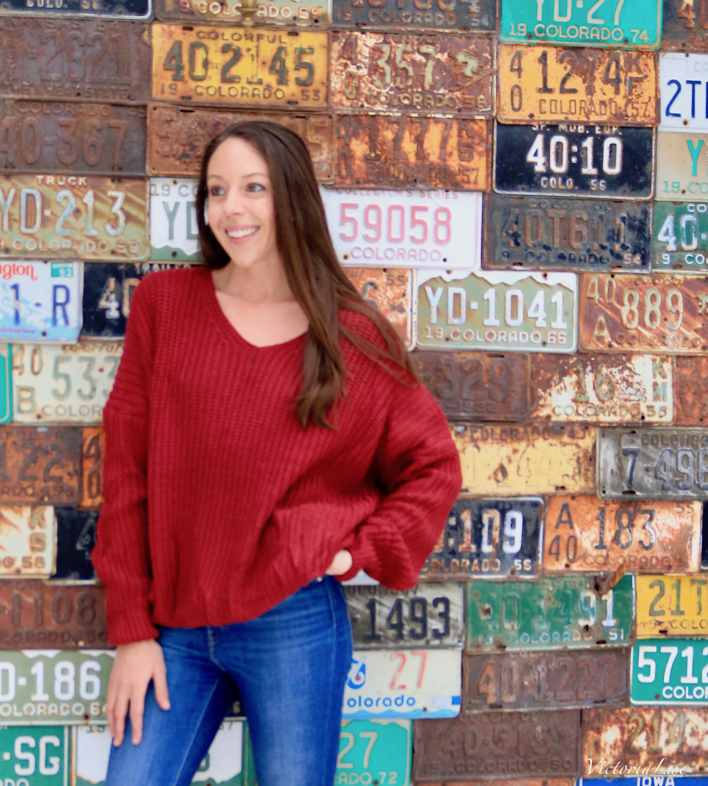 Victoria Lise wears red sweater from Crested Butte Tobacconist in front of iconic Crested Butte, CO building.