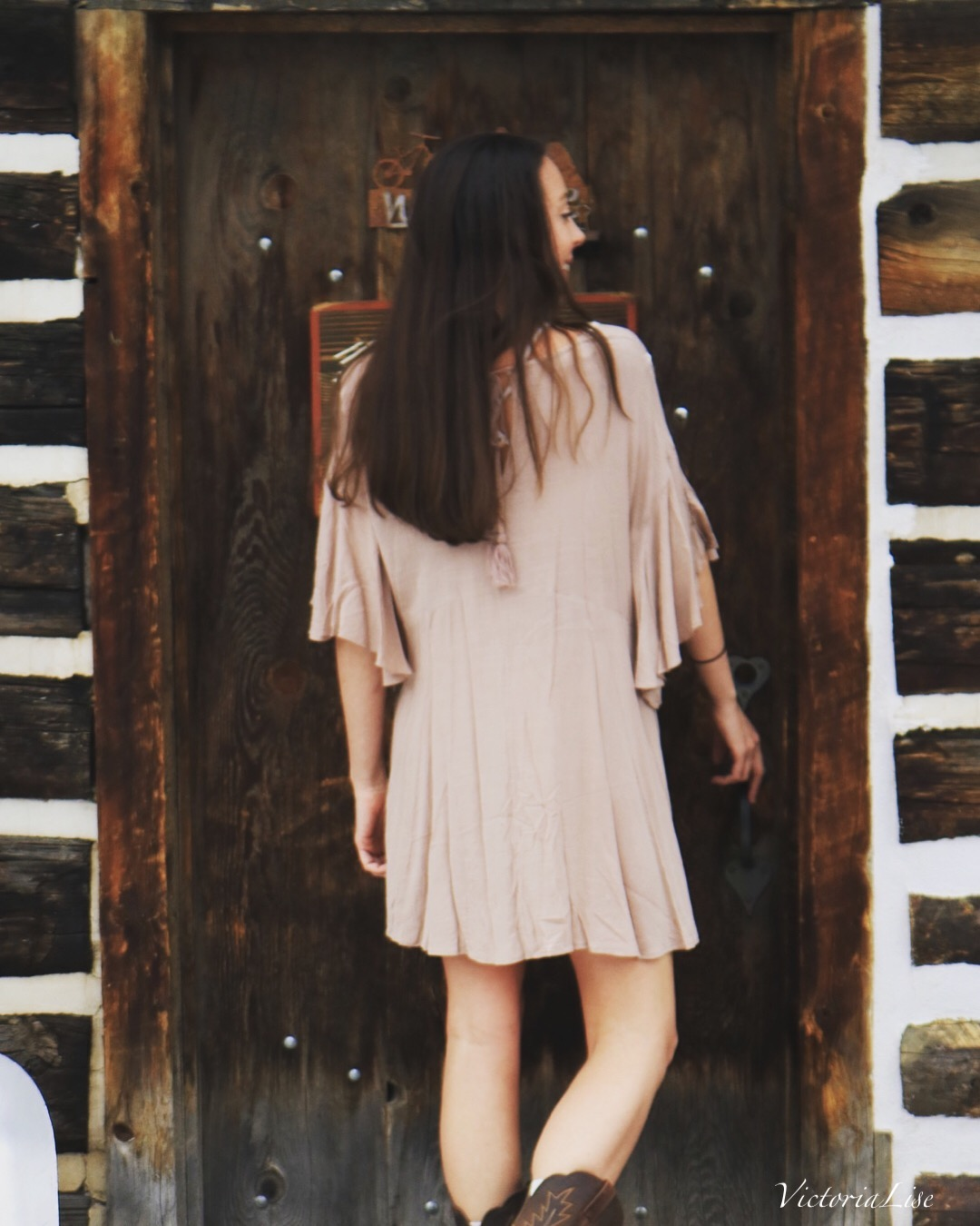 Victoria Lise models ruffled dress in front of authentic Colorado cabin.