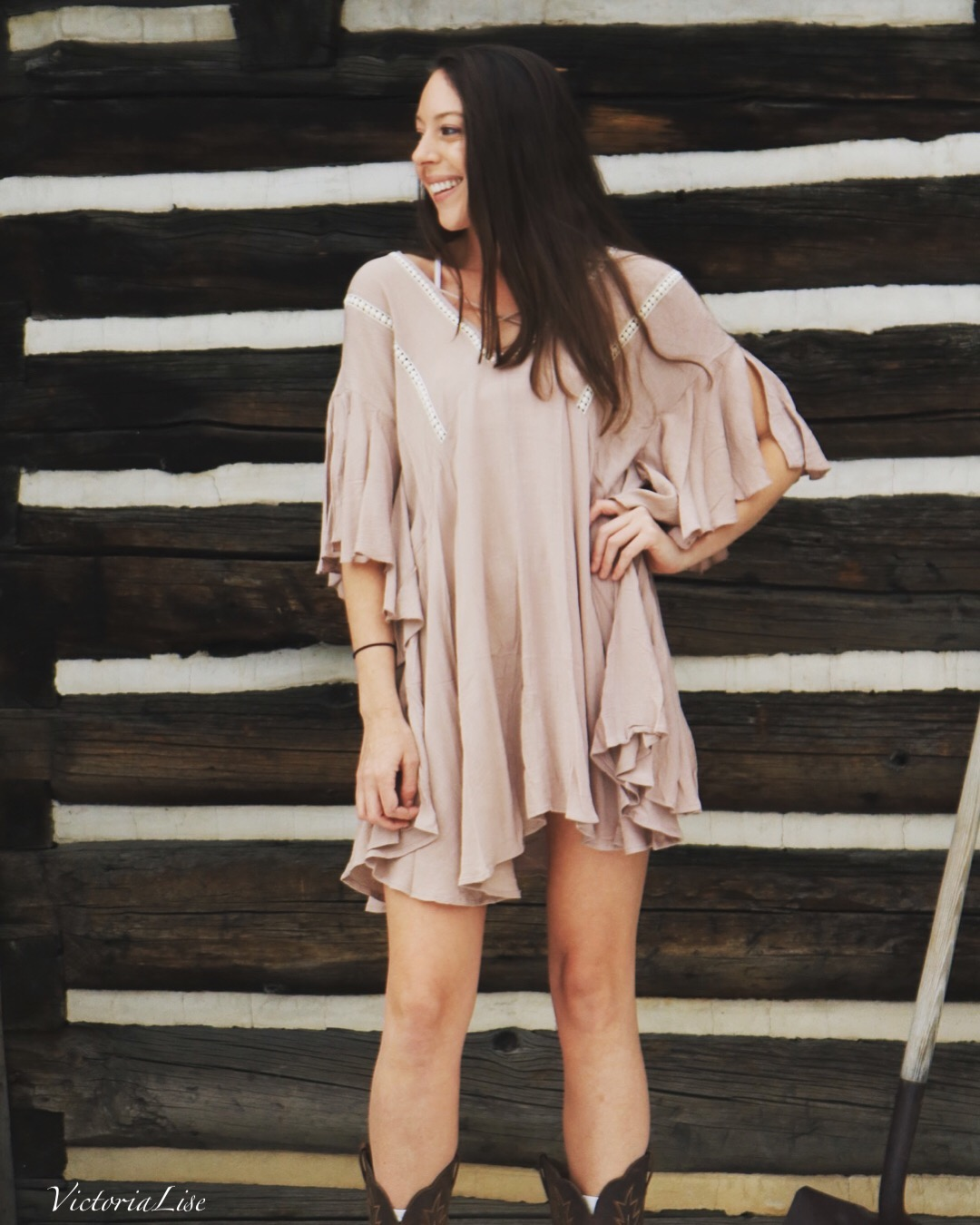 Victoria Lise wars ruffled, trendy dress in from of authentic Colorado cabin.