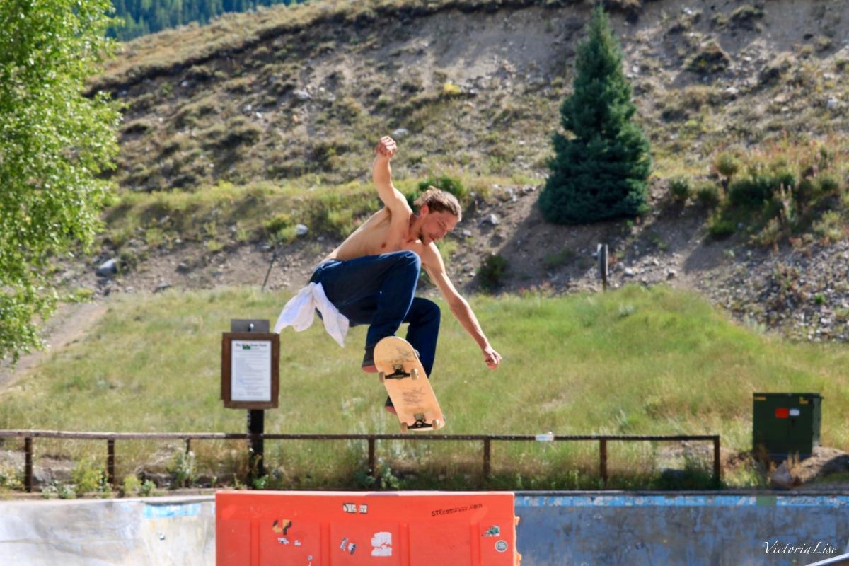 Alex T flys over barrier on skateboard. ©Victoria Lise 2017