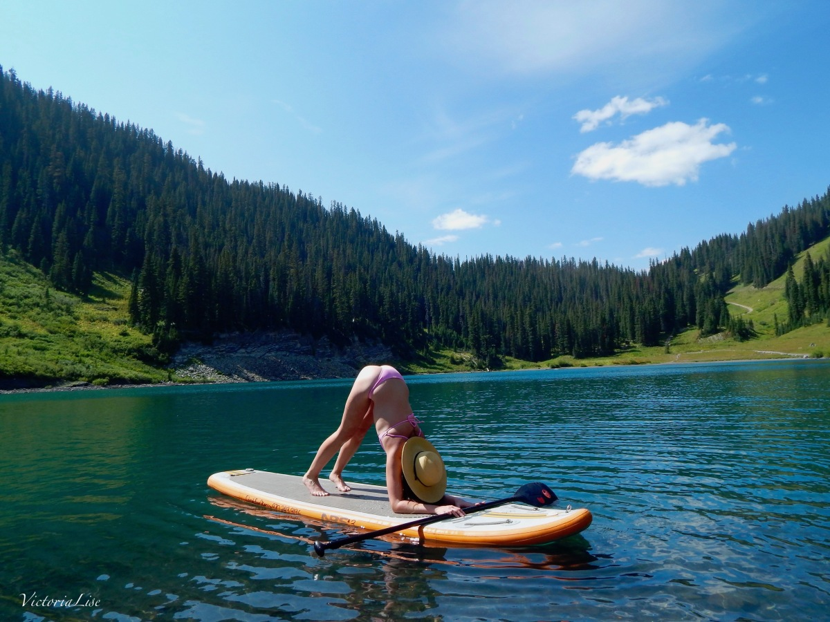 Victoria Lise practicing dolphin pose on Emerald Lake, Colorado.