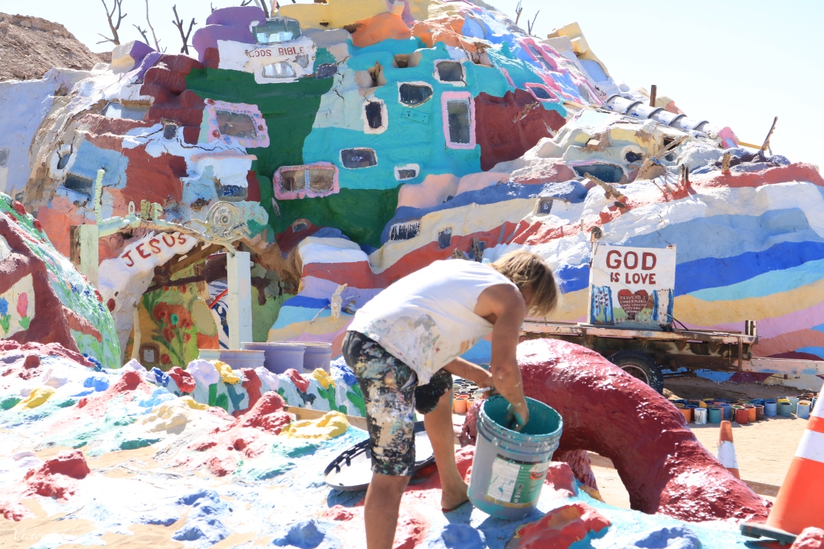 Volunteer, Ron, touches up paint at Salvation Mountain. ©Victoria Lise 2018.
