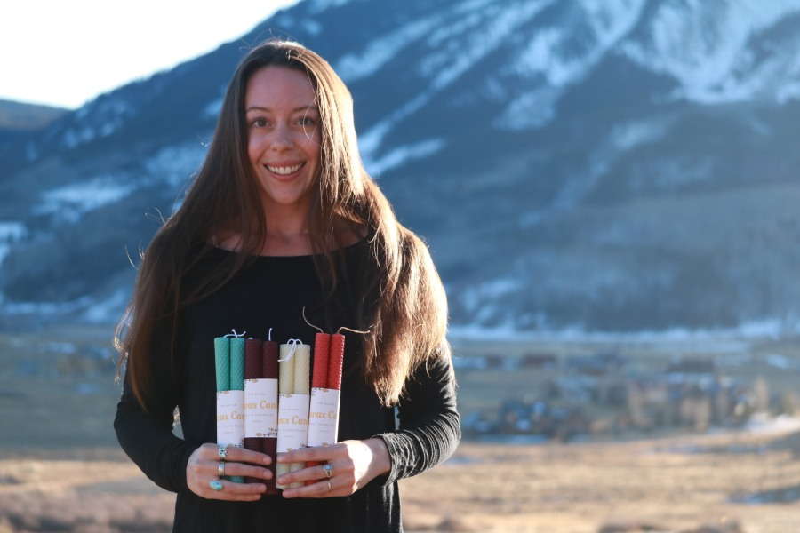 Victoria Lise holding sets of her hand rolled and labeled candle sets for sale.
