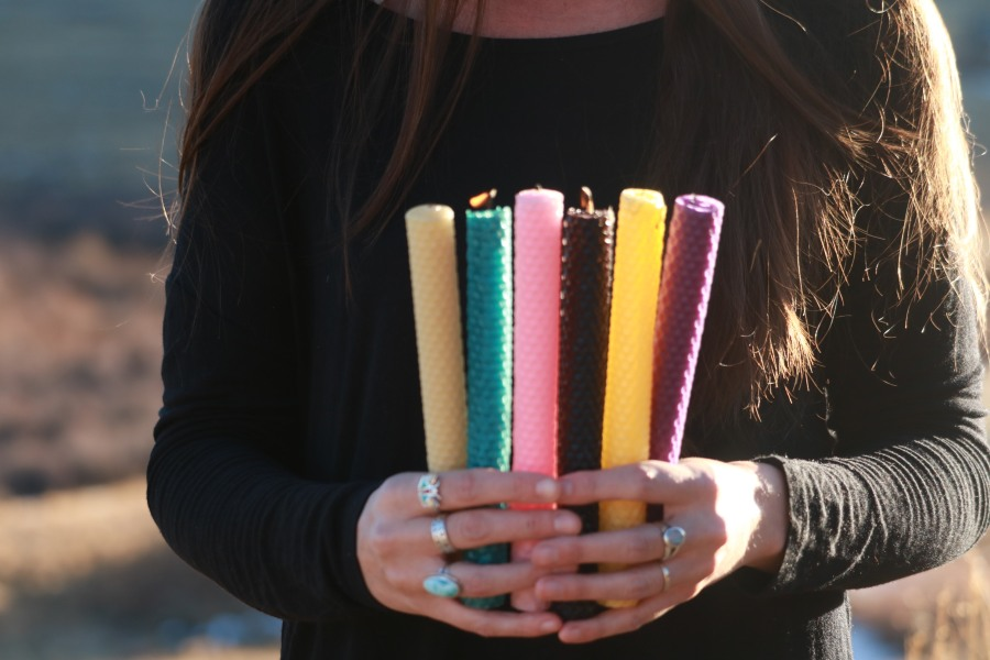 Victoria holding 6 different colors of hand rolled beeswax candles. Showing different colors that are for sale.