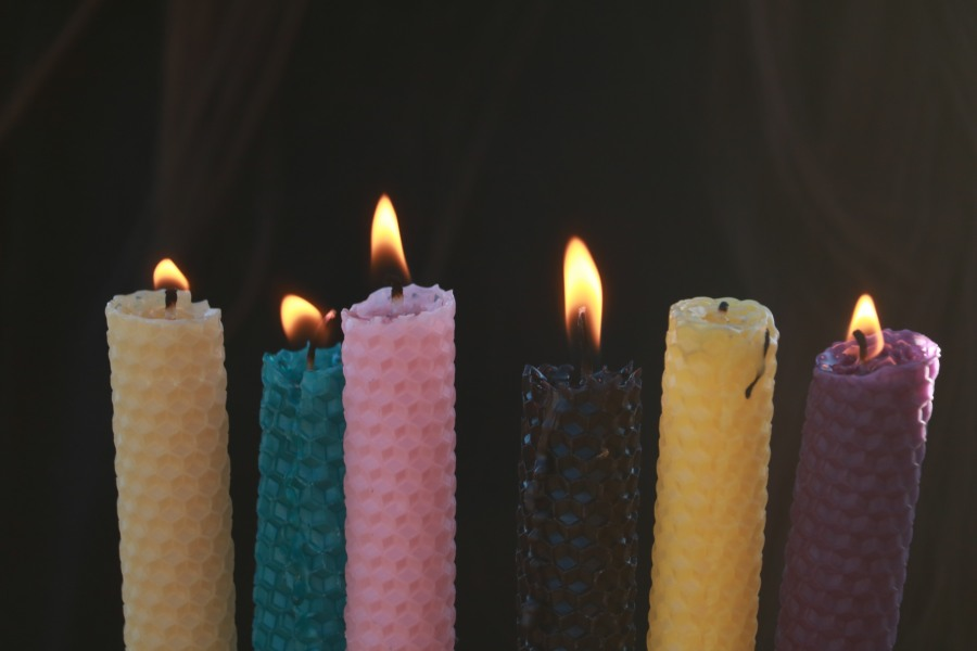 Hand rolled beeswax candles aflame to show the beauty of how they burn. Can be purchased in shop.